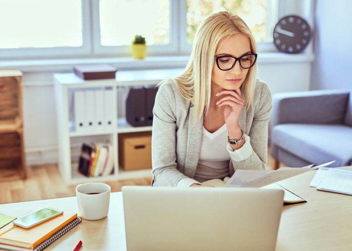 Thoughtful woman reading financail documents while working with